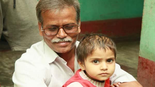 Nand Kishore Sharmaji holds a child